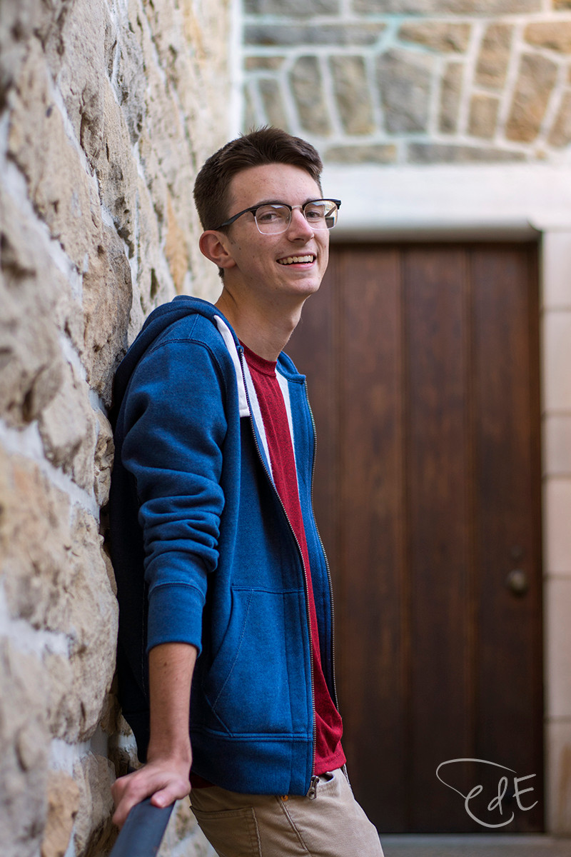Senior picture of high school guy with stone wall