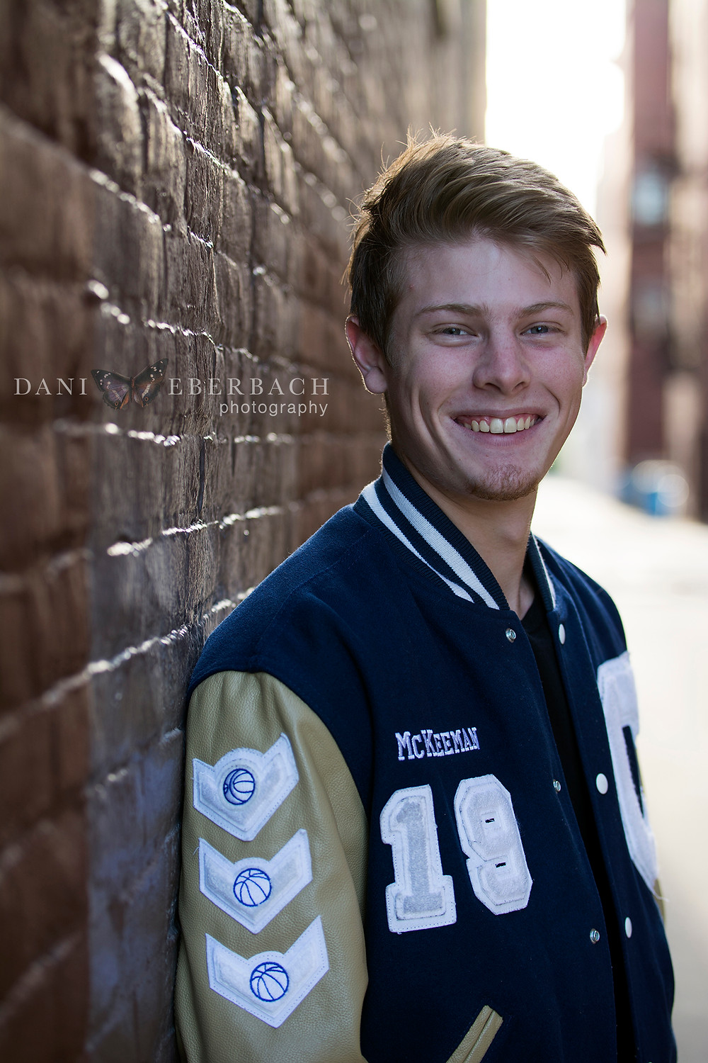 Fort Wayne senior portrait in letter jacket with brick wall