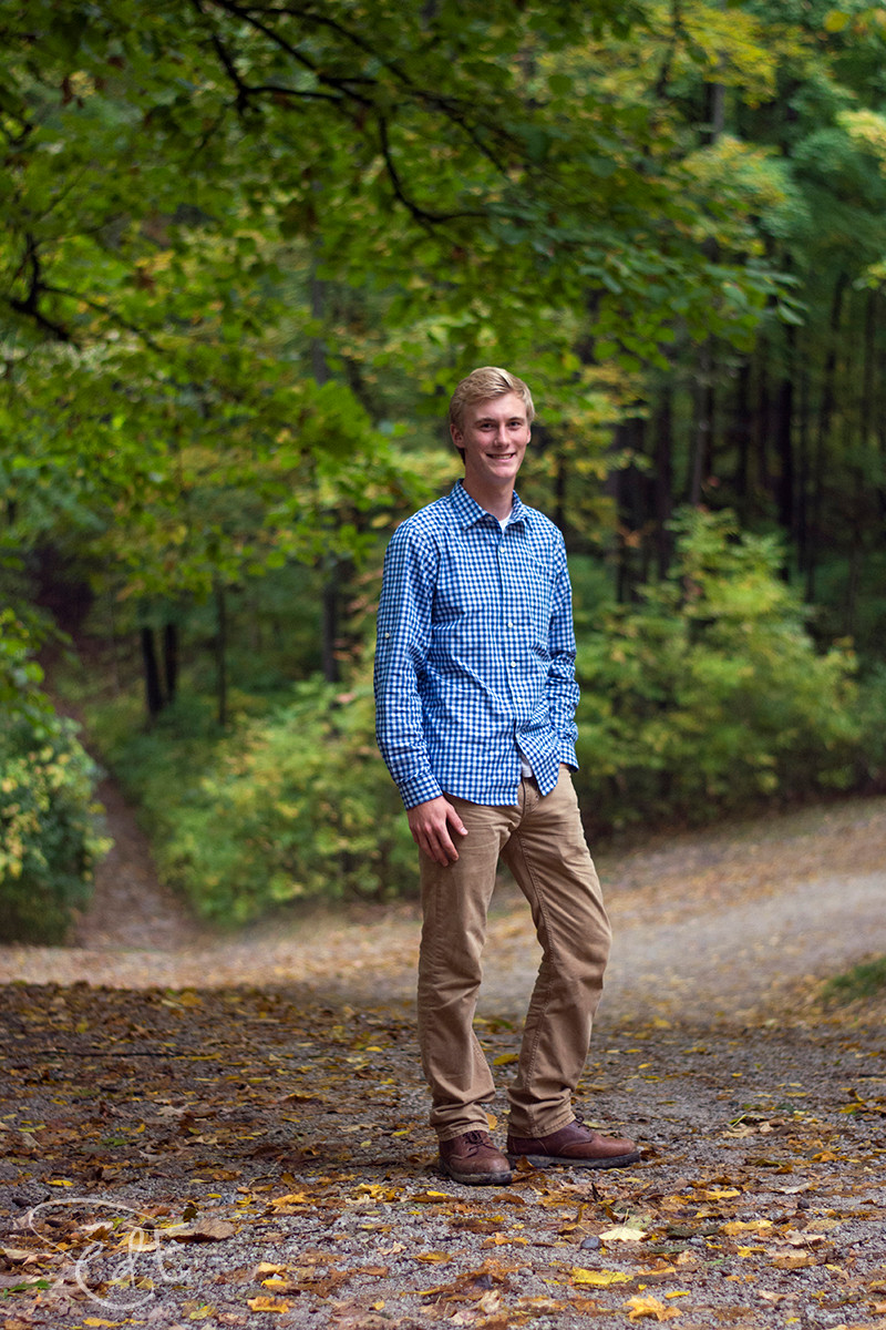 Male senior portrait standing on wooded path