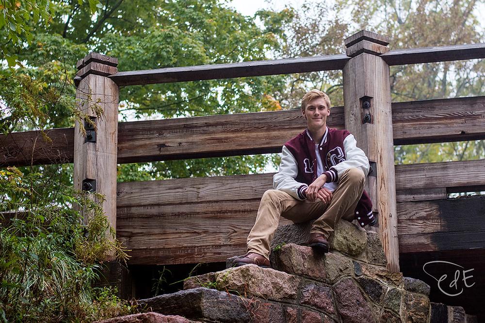 High school senior guy in letter jacket by wooden bridge