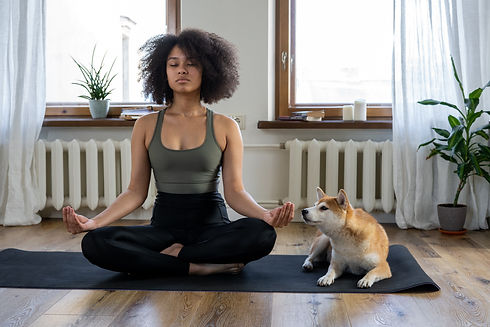 Woman and dog practicing mindfulness, meditation, and donation based yoga in Austin