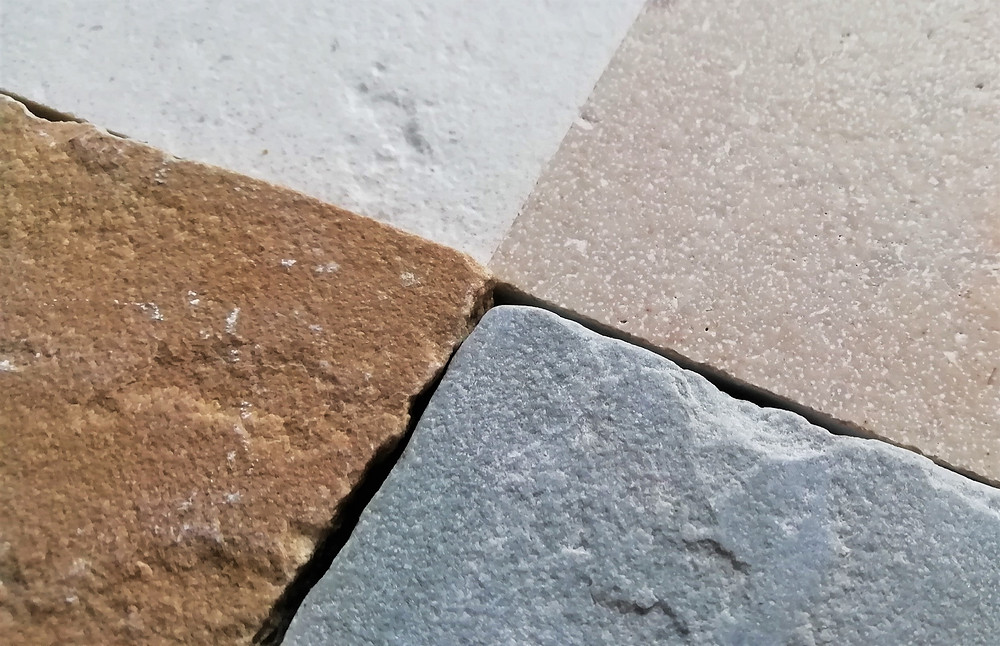 Close up of the texture of natural stone paving showing sawn vs riven paving