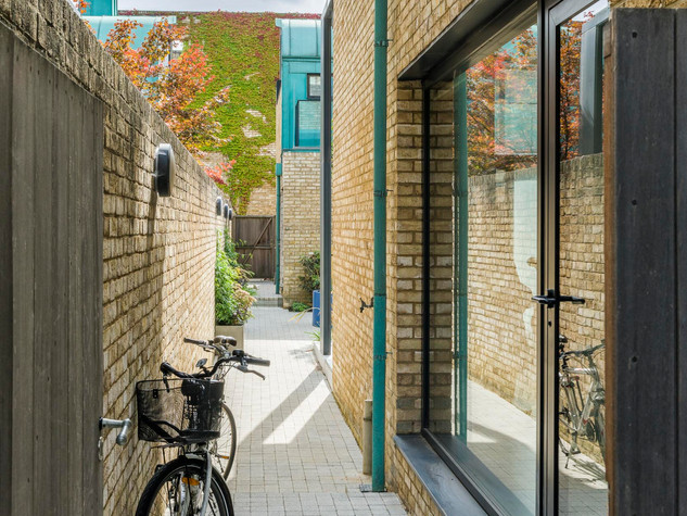 View of an alley with a bicycle leading to a cambridge courtyard garden