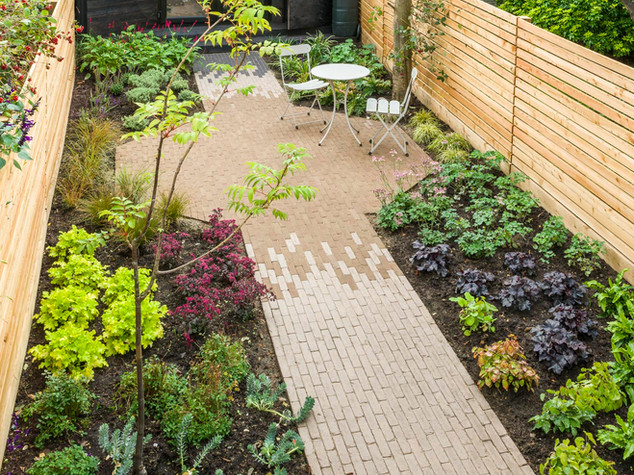 Professionally designed garden in cambridge with clay paver brick path and patio and slatted cedar fencing