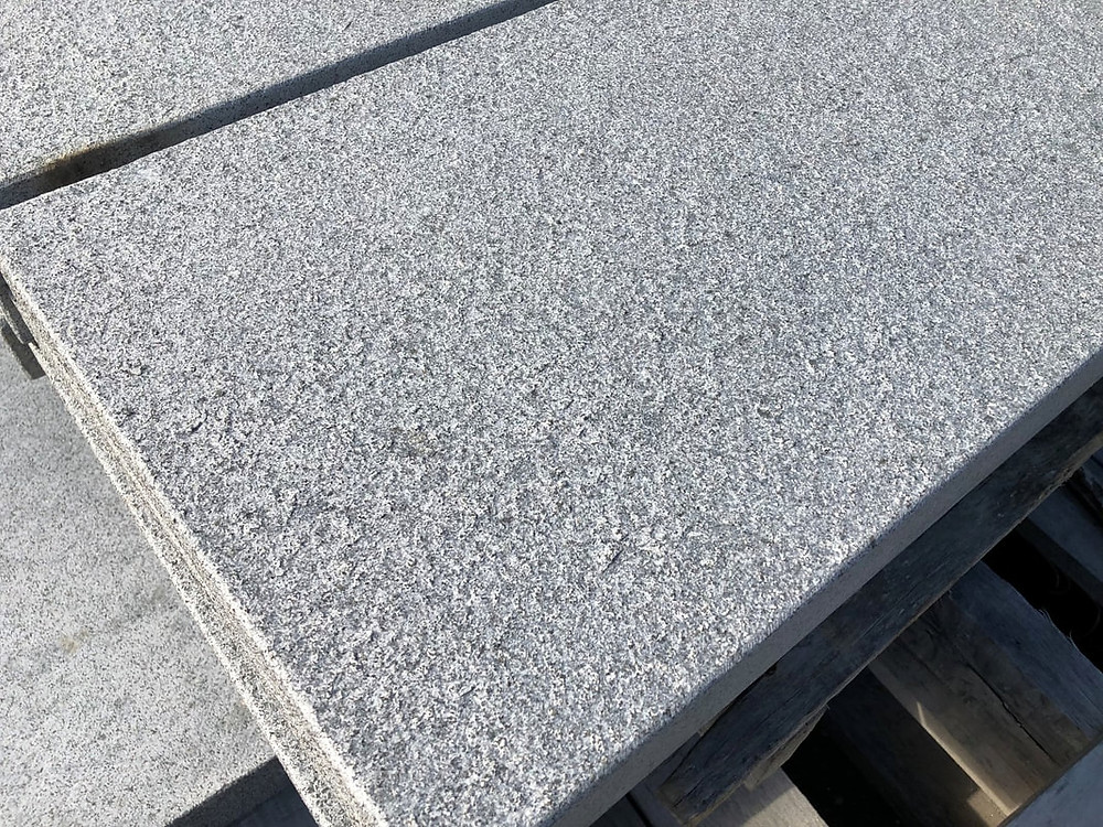 Close up including edge of sawn granite paving showing the flamed surface