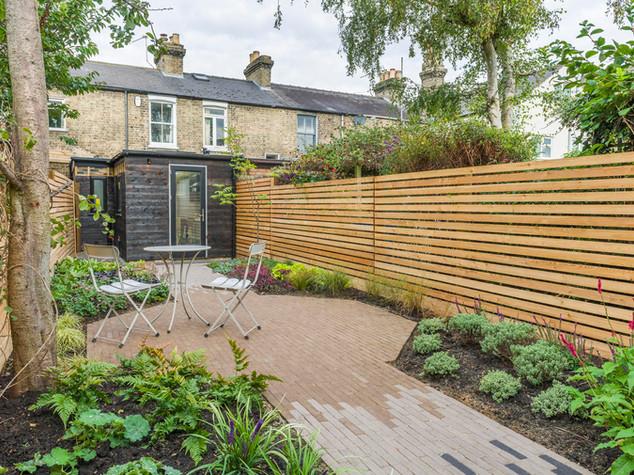 modern garden design using dutch clay bricks and slatted cedar fencing