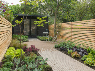Modern garden in cambridge with linear wooden fencing and clay paver path and patio