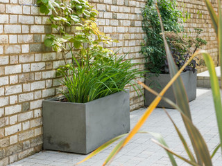 Two polished concrete planters against a brick wall in Cambridge