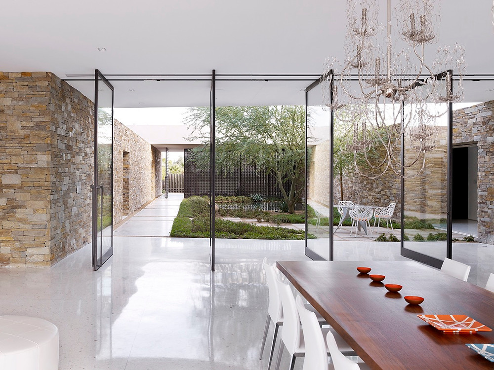 A sleek and stylish contemporary house with open doors onto a minimalist courtyard garden
