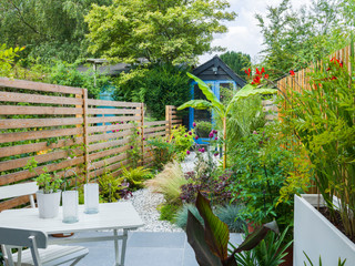 Patio with a small table, lush planting, a white planter and a slatted cedar fence behind