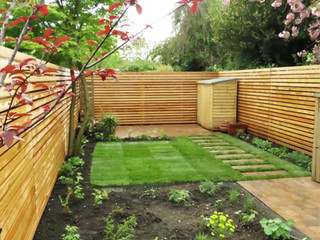 Recently landscaped garden with turf and block paving in a modern stack bond
