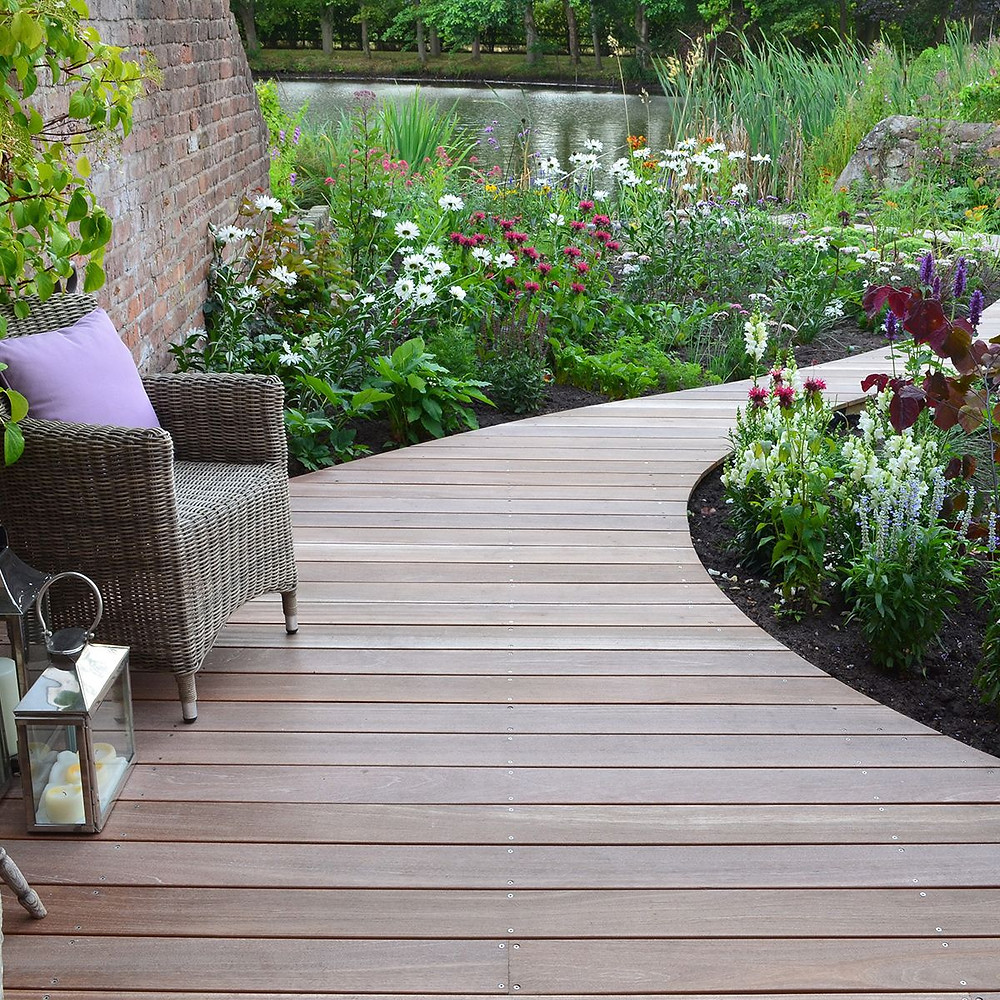 Beautful; hard wood decking path, which curves into the distance past flower beds