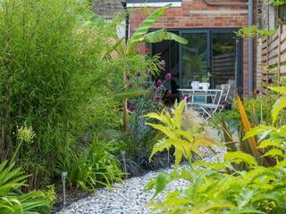A view through foliage towards a patio in a stylish small garden