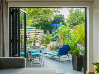 View of a garden from inside the house through bifold doors.  Sun lounger, table and chairs  and exotic planting. Cambridge England