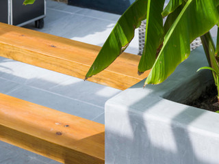 Close up of polished concrete raised beds, a double height bench and a hardy banana tree