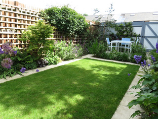 Small family garden with lawn surrounded by sawn limestone paving and contemporary panting scheme