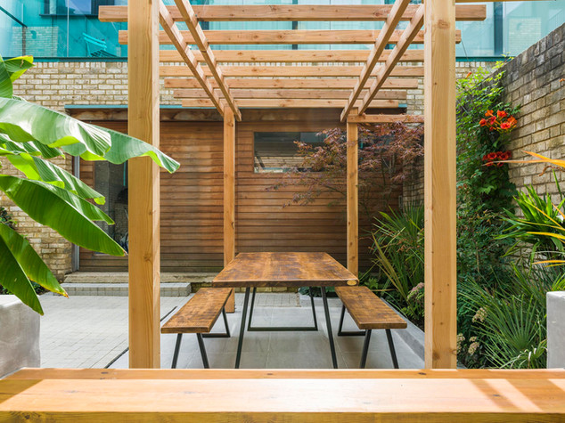 Modern larch pergola with hardwood floating bench and tropical planting