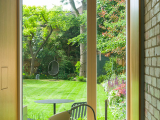 View of a modern garden design through a recessed picture window in cambridgeshire t