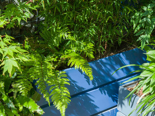 Grey and blue fibreglass planters as part of a multi level garden design