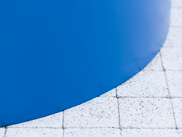 Close up of a round blue GRP fibregalss planter and quare stone setts