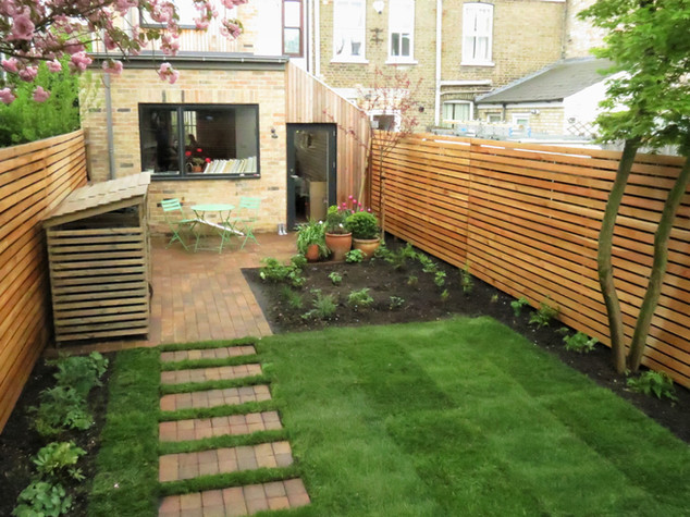 Landscaped family garden with lawn, stepping stones and contemporary horizonatla slatted fencing