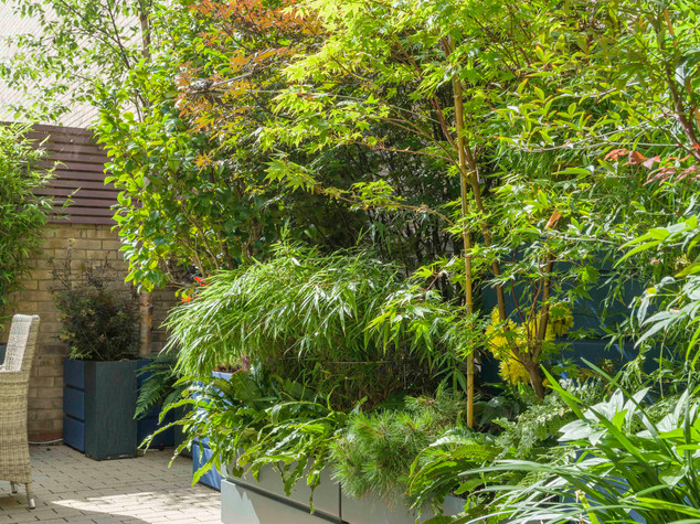 Multi level stacked fibregalss planters in blue and grey colour in a contemporary garden design in cambridge