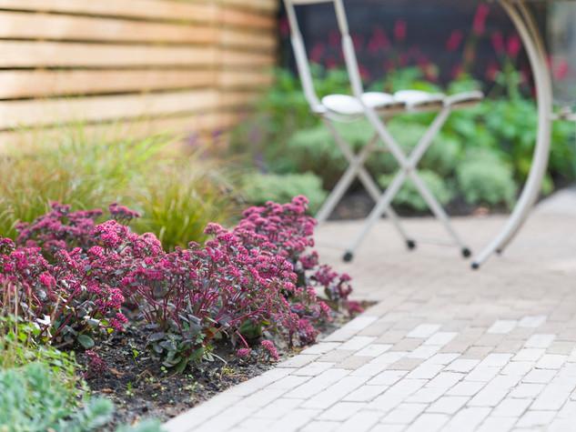 clay paver garden path in cambridge uk with sedum plants and metal garden furniture