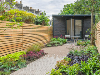 Cedar and larch slatted fencing with a black wooden clad garden studio in a cambridge garden