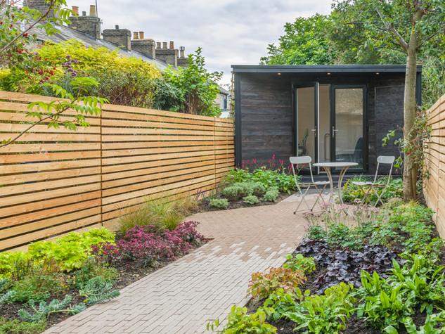 Cedar and larch slatted fencing with a black wooden clad garden studio in a cambridge garden