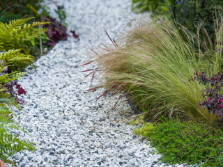 Close up photograph of a winding gravel path with colourful planting each side