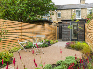 A garden in Cambridge with a brick patio and path, slatted larch fencing and contemporary  planting style
