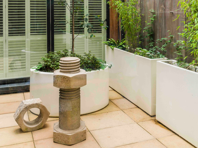 Minimlaist garden design for a courtyard in cambridge.  Sleek white planters with bamboo and flowers, sawn beige sandstone and a contemporary concrete sculpture