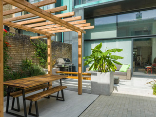 Pergola with modern wooden garden furniture underneath in a courtyard garden in cambridge