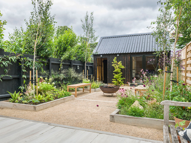 View of cambridge contemporary garden design with a black painted fence, no lawn, limed oak sleepers and a fire bowl