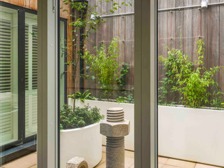 View of hidden courtyard garden in accordia in cambridge with concrete sculpture and minimalist white planters