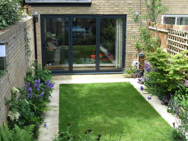 Modern family garden with lawn and sawn paving designed by a garden designer
