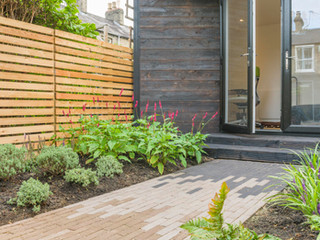 Shou sugi ban clad garden studio with a multicoloured brick garden path  larch slatted fencing and plants