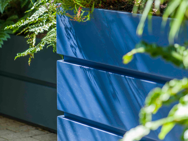 Contemporary blue firbreglass planter on a brick patio