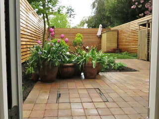 Landscaped garden in cambridge with horizonal larch batten fencing and block paving in a stack bond