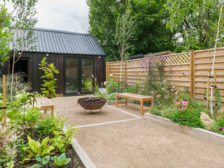 View of a landscaped cambridge garden design without a lawn and with oak sleepers making raised beds