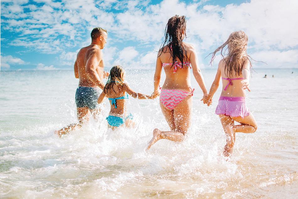 Family running in surf