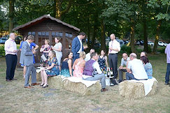 Wedding guests sitting on straw bales