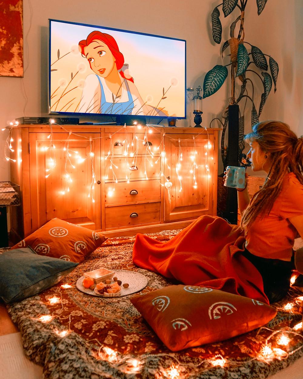 Hannah wie sie sich im Fernsehen einen Film ansieht. Im Hintergrund sieht man Lichterketten und es ist eine weihnachtliche, kuschelige Stimmung.