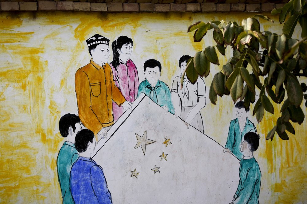 A mural depicting Uighur and Han Chinese men and women carrying the national flag of China in Hotan.