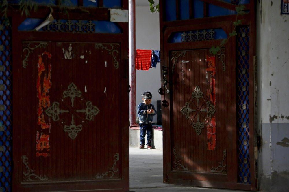 A Uighur child in a courtyard home in Hotan.