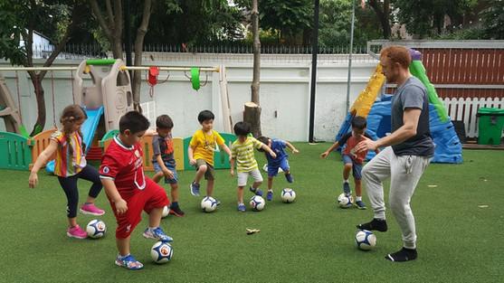 Storytime Preschool students play football