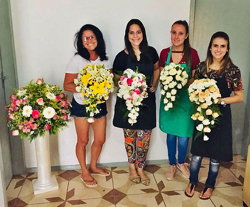 Alunas do curso de arte floral segurando arranjos