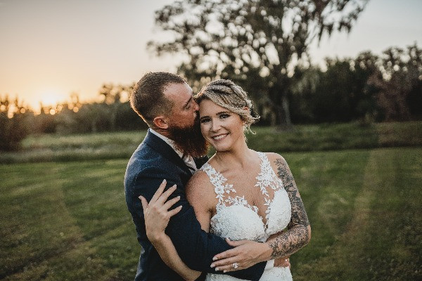 groom kissing his brides cheek during sunset