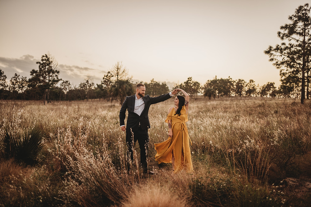 man twirling woman in a field at sunset