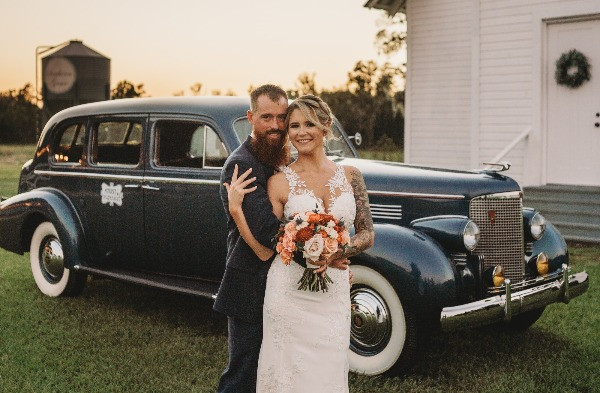 newly weds holding each other in front of an old car